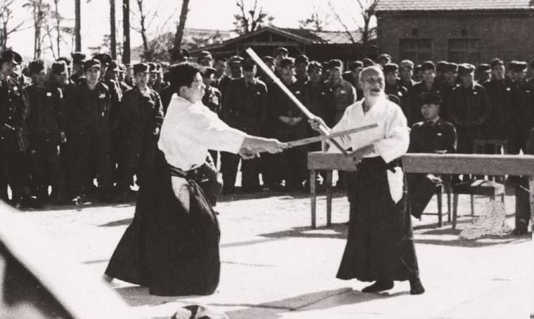 Morihei Ueshiba demonstrating before Self-Defense Force members c. 1955 with Morihiro Saito as uke