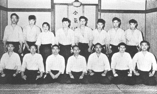 Front row left to right: Hiroshi Tada, Shigenobu Okumura, Kisaburo Osawa, Kisshomaru Ueshiba, Koichi Tohei, Sadateru Arikawa, unknown. Back row left to right: unknown, Seiichi Sugano, Fukiko (Mitsue) Sunadomari, Nobuyoshi Tamura, Masamichi Noro, Yasuo Kobayashi, Kazuo Chiba, Mitsunari Kanai. Photo taken c. 1961 at old Aikikai Hombu Dojo in Tokyo.