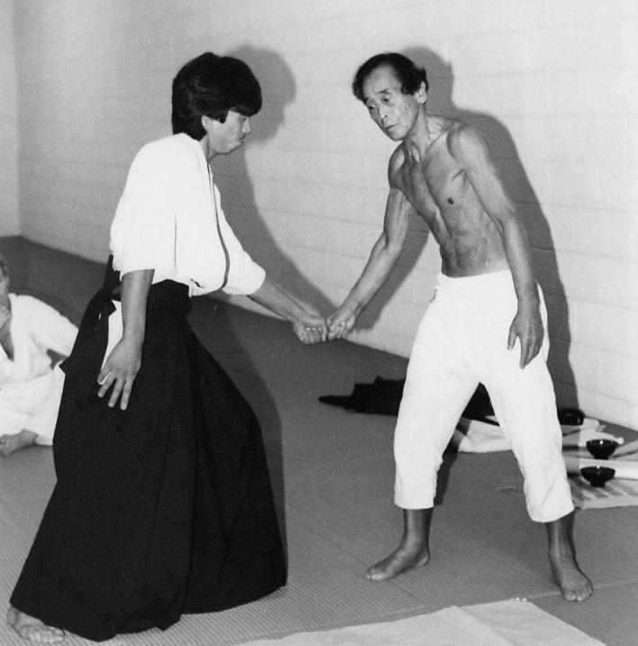 Abe Sensei showing Matsuoka Sensei how to connect breath with body movement.