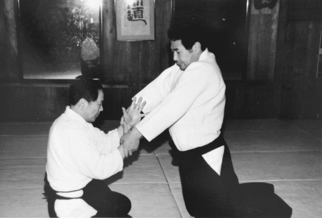 Headmaster Tokimune Takeda instructs Katsuyuki Kondo Sensei in a seated technique c1980