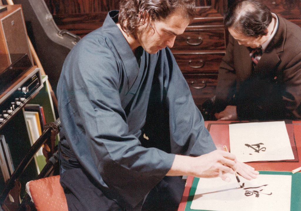 Steven Seagal practicing calligraphy under the guidance of Seiseki Abe.